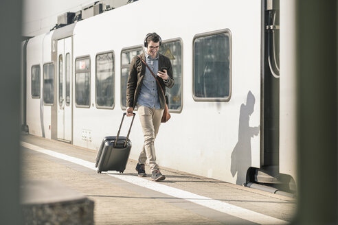 Smiling young man with headphones, cell phone and suitcase walking at station platform - UUF16818