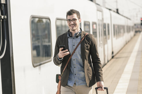 Smiling young man with cell phone at station platform - UUF16821