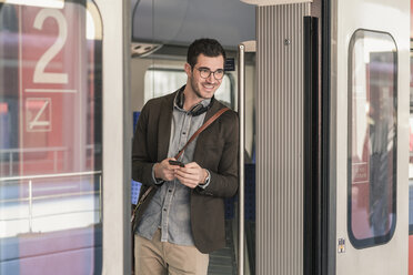 Smiling young man with cell phone in commuter train - UUF16824