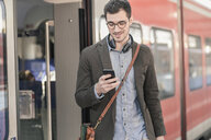 Young man using cell phone at commuter train - UUF16827