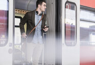 Young man with cell phone in commuter train - UUF16830