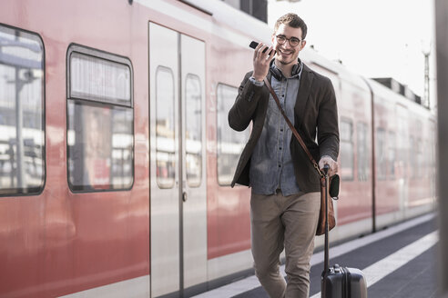 Happy young man with cell phone walking on station platform along commuter train - UUF16836