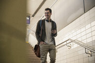 Smiling young man with cell phone walking down stairs at the station - UUF16839