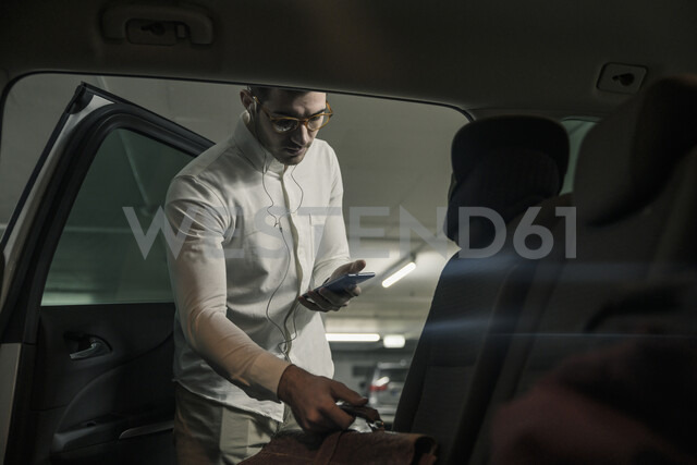 Young man with cell phone and earphones taking bag out of car - UUF16845 - Uwe Umstätter/Westend61