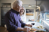 Affectionate senior couple laughing cooking and drinking wine in kitchen - HEROF30172