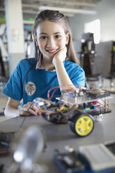 Portrait confident pre-adolescent girl assembling robotics in classroom - HEROF30240