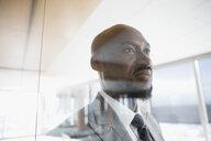 Pensive businessman at window looking away - HEROF30255
