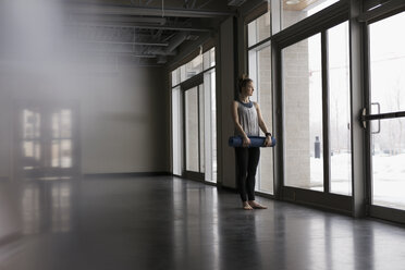 Pensive woman holding yoga mat and looking out window in gym studio - HEROF30282