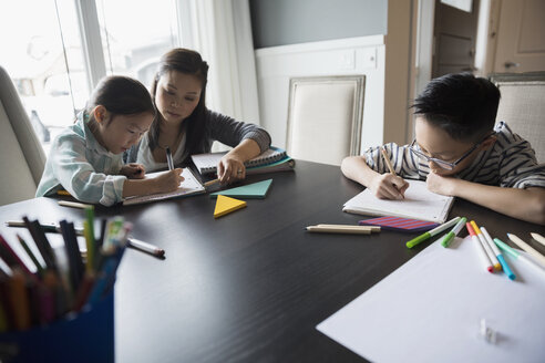 Mother helping daughter with homework at table - HEROF30312