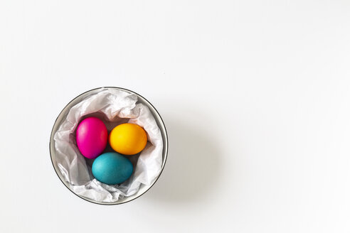 Three dyed Easter eggs in a bowl on white bachground - MELF00204