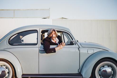 Portrait of senior man leaning out of window of vintage car - OCMF00319