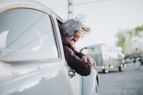 Senior man leaning out of window of vintage car screaming - OCMF00325