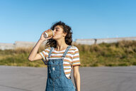 Young woman drinking coffee from a disposable cup - AFVF02612