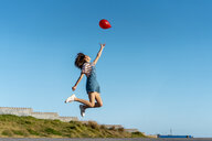 Jumping young woman, letting go of a red ballon - AFVF02621