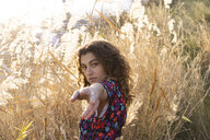 Young woman standing in meadow, reaching out with her hand - AFVF02624