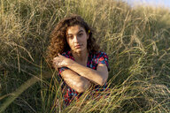 Pensive young woman crouching in meadow - AFVF02633