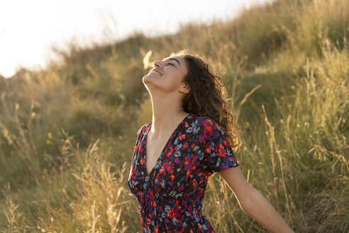 Happy young woman standing in summer meadow - AFVF02636