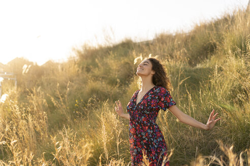 Happy young woman standing in summer meadow - AFVF02639
