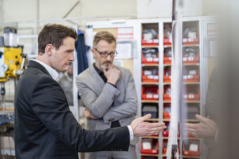 Two businessmen discussing plan in a factory - DIGF06218