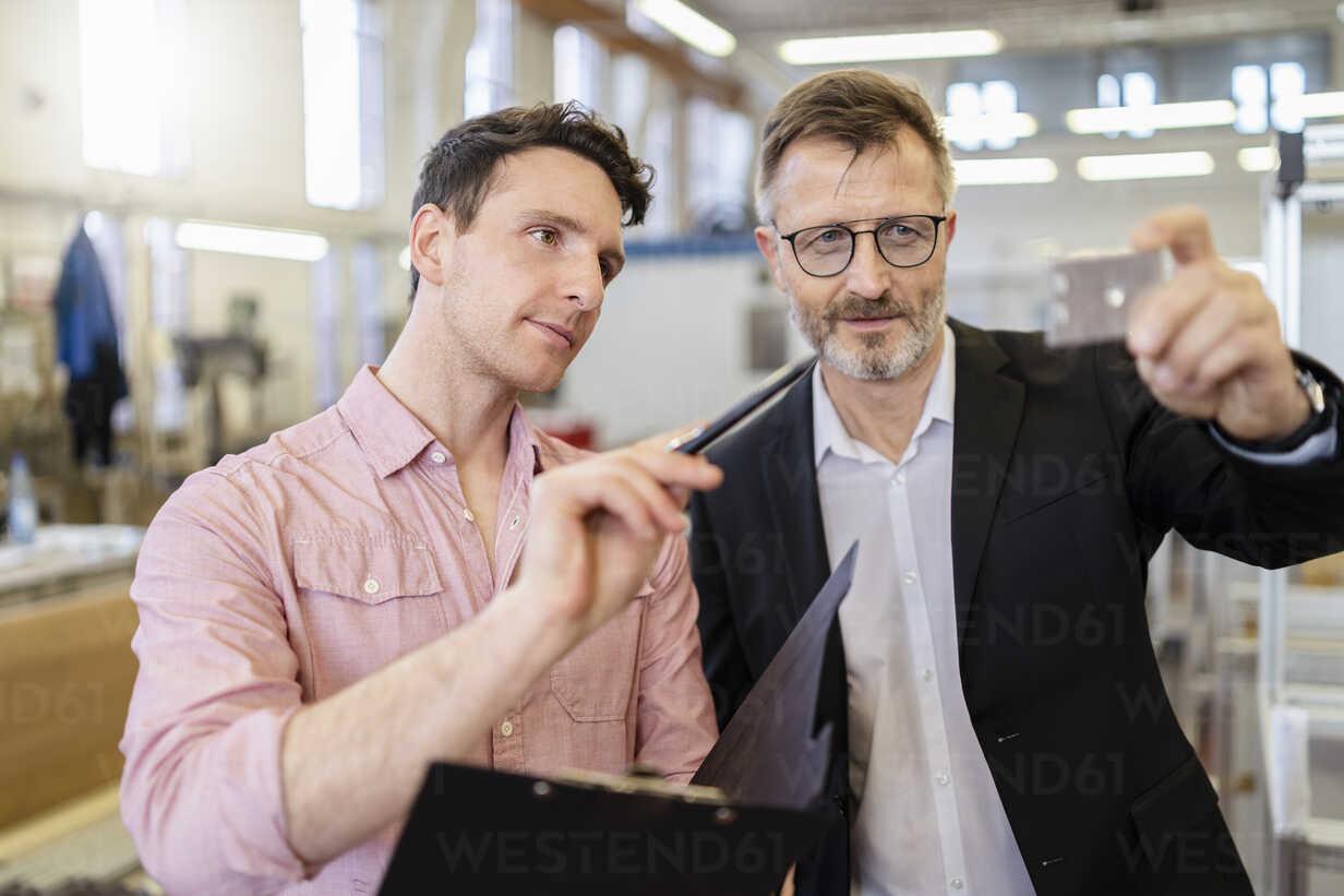 Two men in factory examining workpiece - DIGF06245 - Daniel Ingold/Westend61