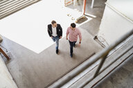 Bird's eye view of two men walking at loading bay in a factory - DIGF06257