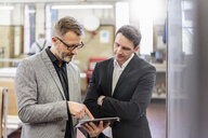 Two businessmen with tablet discussing in a factory - DIGF06284