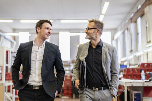 Two smiling businessmen talking in a factory - DIGF06287
