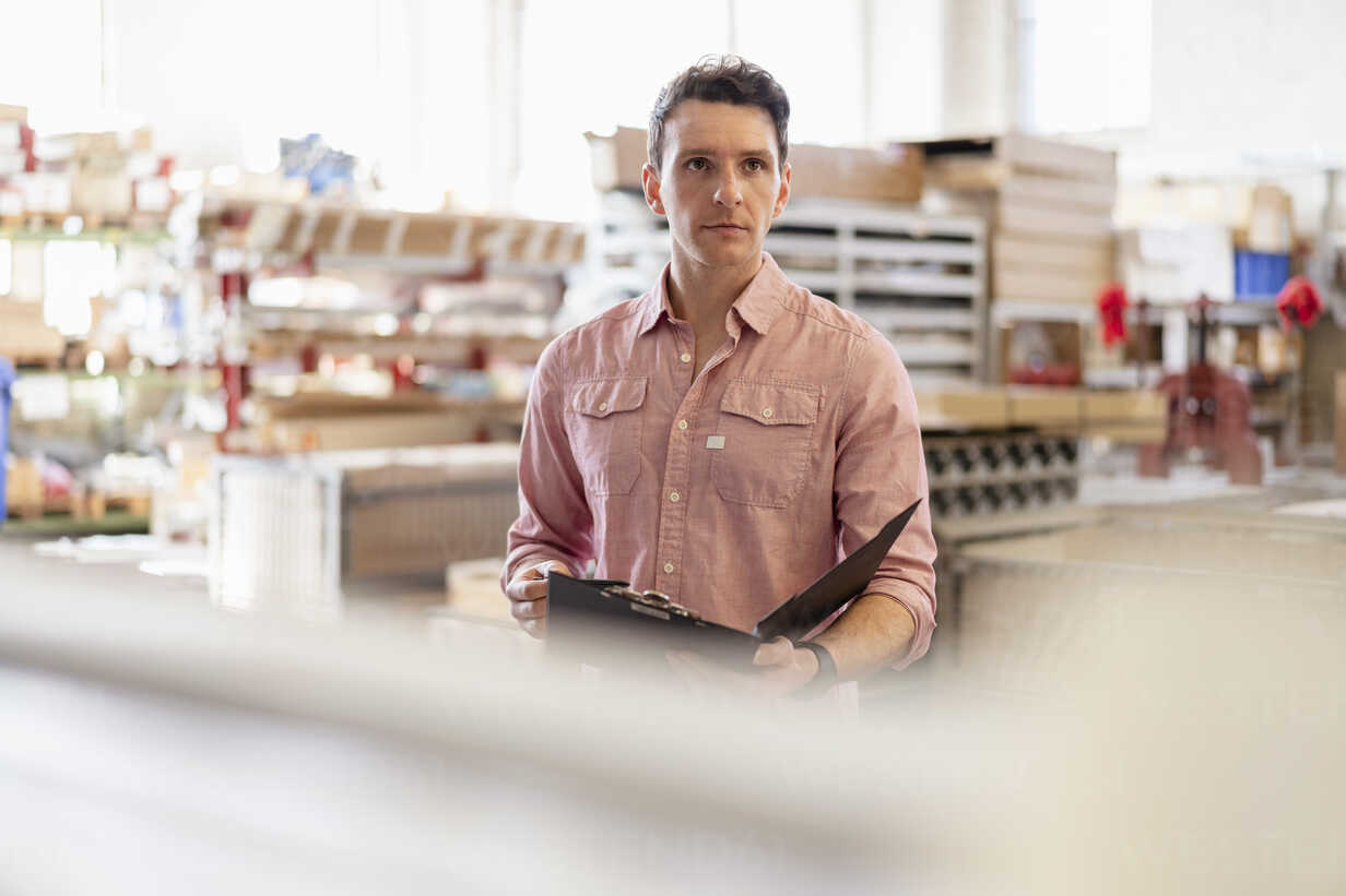 Man with clipboard in factory warehouse - DIGF06299 - Daniel Ingold/Westend61