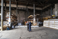 Two businessmen with folder talking in an old storehouse - DIGF06326