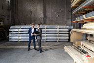Two businessmen with folder talking in an old storehouse - DIGF06329