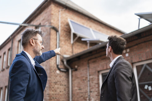 Businessman pointing at solar panels on brick building - DIGF06332