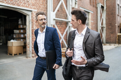 Two businessmen walking and talking at an old brick building - DIGF06335