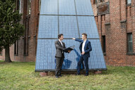 Two businessmen talking outside brick building at solar panels - DIGF06341