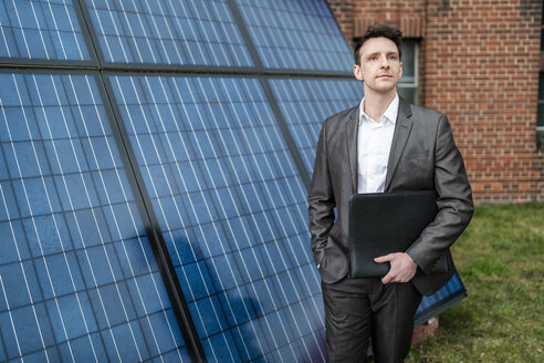 Businessman holding folder standing in front of solar panels - DIGF06344