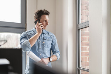 Businessman on cell phone at the window in office - DIGF06365