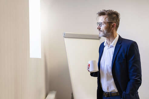 Businessman holding cup of coffee in office - DIGF06374