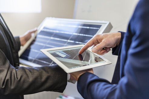 Close-up of two businessmen in office with solar cell and tablet - DIGF06380