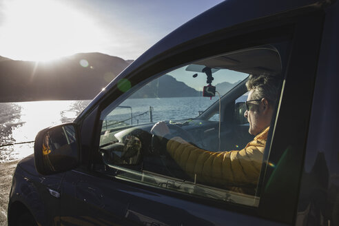 Man sitting in the car while crossing the lake on the ferry. Como, Italy. - MRAF00368