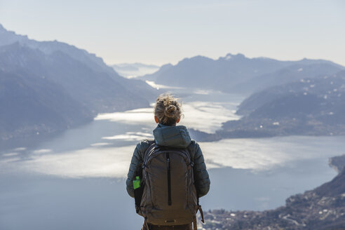 Italy, Como, Lecco, woman on a hiking trip in the mountains above Lake Como enjoying the view - MRAF00371