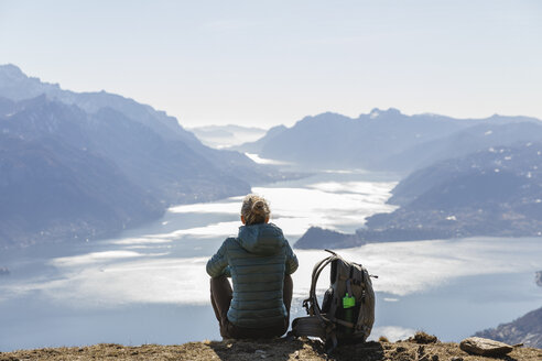 Italy, Como, Lecco, woman on a hiking trip in the mountains above Lake Como sitting down enjoying the view - MRAF00374