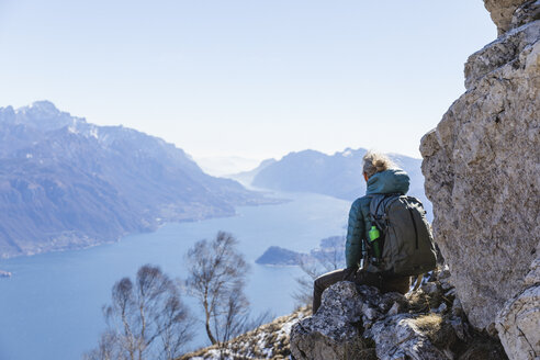 Female hiker looking at the lake landscape from the mountain. Como, Lecco. - MRAF00383