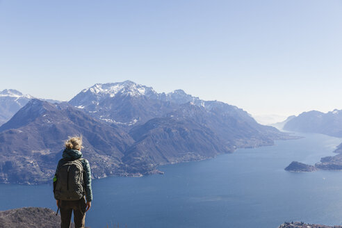 Italy, Como, Lecco, woman on a hiking trip in the mountains above Lake Como enjoying the view - MRAF00389