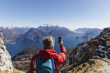 Italy, Como, man on a hiking trip in the mountains above Lake Como taking photo with cell phone - MRAF00398