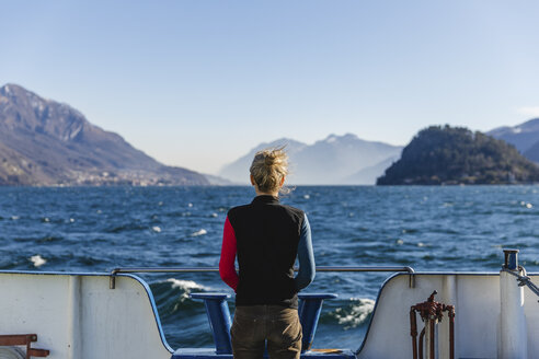 Italy, Como, rear view of woman on the ferry enjoying the view of Lake Como - MRAF00401