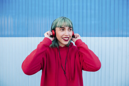 Portrait of smiling young woman with blue dyed hair listening music with headphones - LOTF00064