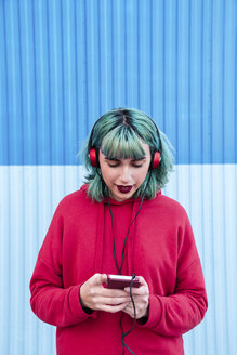Portrait of young woman with blue dyed hair listening music with headphones looking at smartphone - LOTF00067