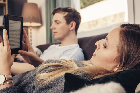 Young couple relaxing on sofa and using notebook and ebook reader - SEBF00094