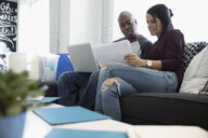 Couple with laptop discussing financial paperwork in living room - HEROF30406