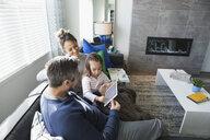 Family using digital tablet on living room sofa - HEROF30421