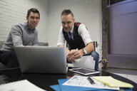 Businessmen meeting working at laptop in office - HEROF30469